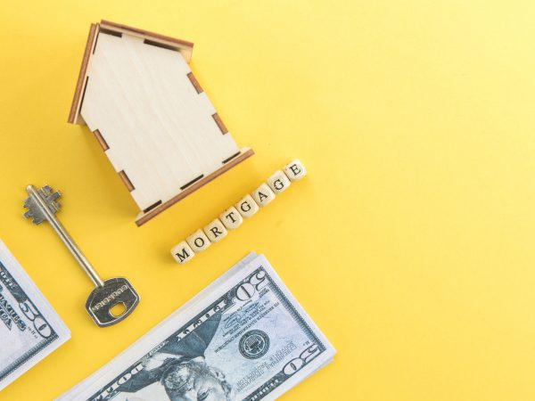 mortgage, loan and home purchase. Model of house, dollar bills, key on white and yellow isolated background. Free space for text, flat layout