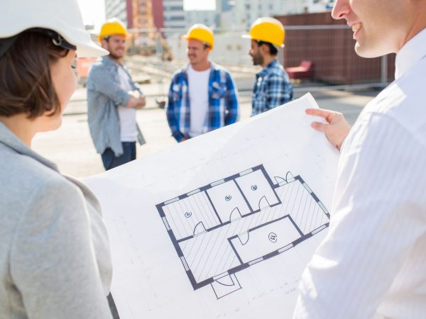 construction, architecture, business, teamwork and people concept – close up of architects with blueprint at building site