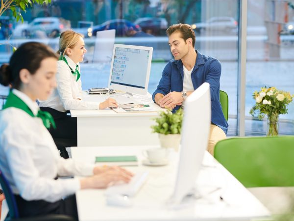 Cheerful attractive bank sales consultant in corporate outfit sitting at table with computer and showing magazine with bank products to customer while working with him in office.