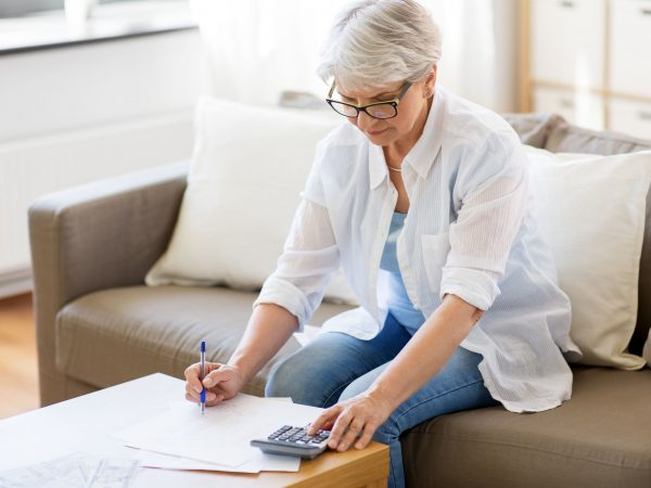 business, savings, annuity insurance, age and people concept – senior woman with papers or bills and calculator writing at home