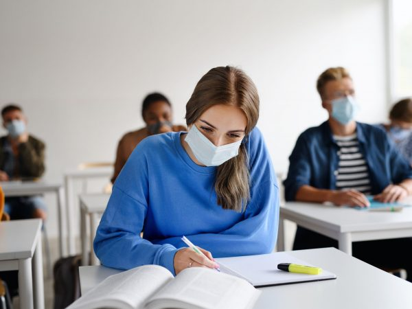 Front view of young students with face masks at desks at college or university, coronavirus concept.