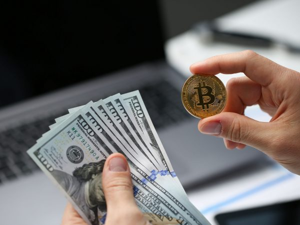 Male hand holds bitcoin and dollar coin on the background of the laptop keyboard