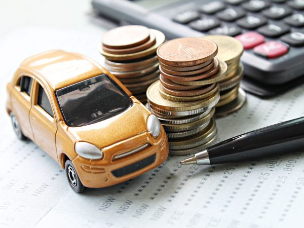 88327269 – business, finance, saving money or car loan concept : miniature car model, coins stack, calculator and saving account book or financial statement on desk table