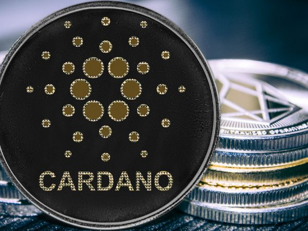 Coin cryptocurrency Cardano on the background of a stack of coins. ADA