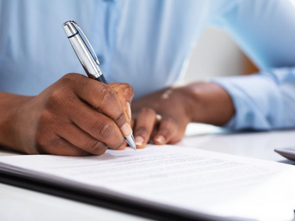 Close-up Of A Businesswoman's Hand Filling Contract Form