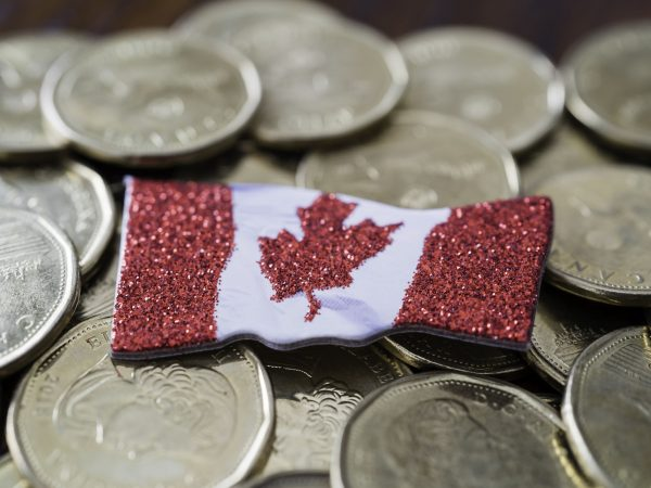 Canadian one dollar coins with a canadian flag on top