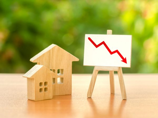 Wooden houses and an easel red arrow down. The fall of the real estate market. concept of value or cost decrease. low liquidity and attractiveness. cheap rent. Reduced demand and stagnation.