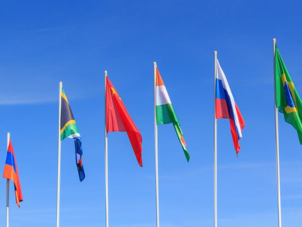 Flags of BRICS countries on a blue sky background
