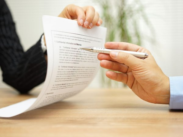 businesswoman holding legal document and  wants an explaination about article in contract