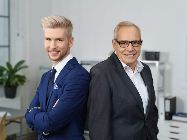 68433247 – confident successful business partners posing together with a stylish young man and his older mentor standing back to back smiling at the camera