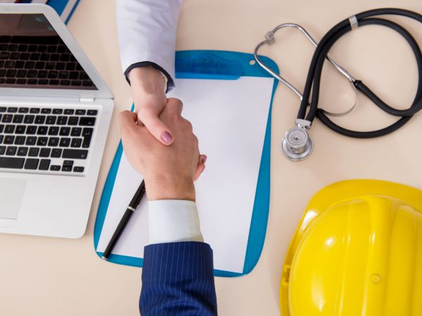 Doctor and manager agreeing industrial insurance coverage